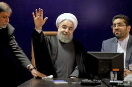 Iranian President Hassan Rouhani (C) waves after registering for February's election of the Assembly of Experts, at the Interior Ministry in Tehran, Dec. 21, 2015.