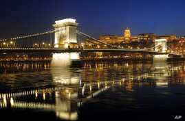 FILE - Ice-floes float under the floodlit Chain Bridge and the Royal Palace in the Castle of Buda in Budapest, Hungary.