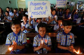 FILE - Students at a school in Ahmadabad, India, hold candles and pray for the Thai youth soccer players and their coach trapped in a cave, July 9, 2018.