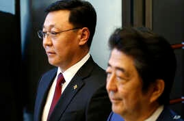 FILE - Mongolian Prime Minister Jargaltulgyn Erdenebat, left, and his Japanese counterpart Shinzo Abe attend a joint press conference following their meeting at Abe's official residence in Tokyo, Oct. 14, 2016.
