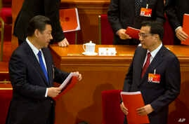 Chinese President Xi Jinping, left, and Chinese Premier Li Keqiang prepare to leave after the closing ceremony of the National People's Congress in Beijing's Great Hall of the People, March 15, 2015.