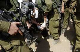Israeli soldiers remove French diplomat Marion Castaing from her truck containing emergency aid, West Bank herding community of Khirbet al-Makhul, Sept. 20, 2013.