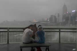 People play with strong wind caused by Typhoon Hato on the waterfront of Victoria Habour in Hong Kong, Aug. 23, 2017. The powerful typhoon barreled into Hong Kong Wednesday, forcing offices and schools to close and leaving flooded streets, shattered