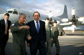 Australian Prime Minister Tony Abbott is guided around a Royal Australian Air Force P-3C Orion aircraft by Australian Air Force Group Commander Craig Heap, second from left, in Bullsbrook, near Perth, Australia,  March 31, 2014.