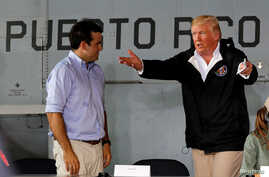 U.S. President Donald Trump talks with Puerto Rico Governor Ricardo Rossello (L)  as they take their seats for a briefing on hurricane relief efforts in a hangar at Muniz Air National Guard Base in Carolina, Puerto Rico, Oct. 3, 2017.
