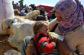 A mother feeds her baby as thousands of new Syrian refugees from Kobani arrive at the Turkey-Syria border  crossing of Yumurtalik near Suruc, Turkey, Wednesday, Oct. 1, 2014. U.S.-led coalition airstrikes targeted Islamic State fighters pressing thei