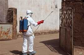 In this photo taken Friday, Nov. 14, 2014, a health worker sprays disinfectant near a mosque, after the body of a man suspected of dying from the Ebola virus was washed inside before being berried  in Bamako, Mali. It all started with a sick nurse, w