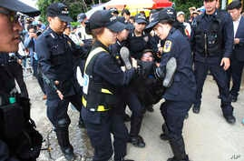 Police officers detain a Buddhist believer near the main gate of the church in Anseong, South Korea, June 11, 2014.