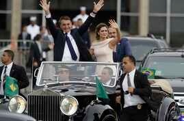 Flanked by first lady Michelle Bolsonaro, Brazil's President Jair Bolsonaro waves as he rides in an open car after his swearing-in ceremony, in Brasilia, Brazil, Jan. 1, 2019.