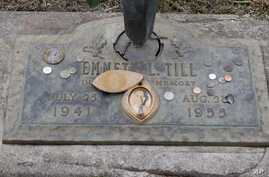 The grave marker of Emmett Till has a photo of Till and coins placed on it during a gravesite ceremony at the Burr Oak Cemetery marking the 60th anniversary of the murder of Till in Mississippi, Aug. 28, 2015, in Alsip, Ill.