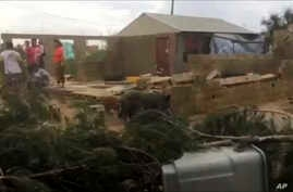 In this image made from a video, people stand near a house damaged by Cyclone Gita in Nuku'alofa, Tonga Tuesday, Feb. 13, 2018.