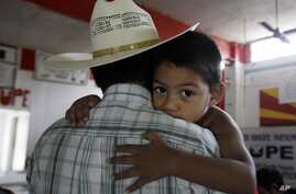 FILE - Miguel, 3, clings to his father, Miguel, an illegal immigrant, in San Juan, Texas, Aug. 27, 2010. Miguel and his wife, who remain in the U.S. as illegal immigrants, have two children born in the U.S.