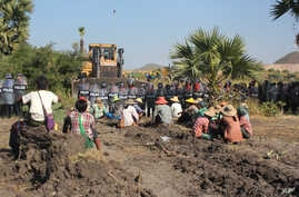 Farmers confront riot police at Letpadaung copper-mine, Monywa in northwestern Myanmar Monday, Dec. 22, 2014.