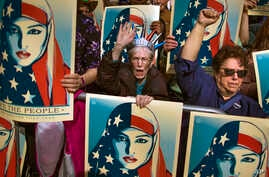 FILE - In this Feb. 19, 2017 file photo, people carry posters during a rally against President Donald Trump's executive order banning travel from seven Muslim-majority nations, in New York's Times Square.