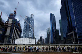 FILE - Office workers walk to the train station during evening rush hour in the financial district of Singapore, March 9, 2015.