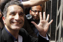 Egyptian television satirist Bassem Youssef waves to his supporters as he enters Egypt's state prosecutors office to face charges  for allegedly insulting Islam and the country's leader, in Cairo, Mar. 31, 2013.