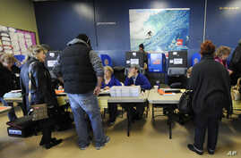Voters sign in to vote at busy polling station at East Elementary School early Tuesday, November 6, 2012, in Long Beach, N.Y., one of several voting locations that were created as a result of Superstorm Sandy.