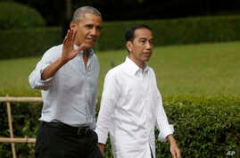 Former U.S. President Barack Obama, left, waves at reporters as he walks with Indonesian President Joko Widodo during their meeting at Bogor Presidential Palace in Bogor, West Java, Indonesia, June 30, 2017.