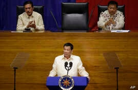 FILE- Philippine President Rodrigo Duterte, center, gestures as he is applauded by Senate President Vicente Sotto, left, and House Speaker Pantaleon Alvarez during his third State of the Nation Address at the House of Representatives in Quezon city,