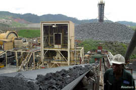 FILE -  A worker at Ashanti Goldfield Company's big mine in Obuasi, Ghana, walks next to a conveyor belt carrying ore up to a processing plant, October 23, 2003.