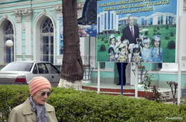 A woman walks past an election board of Uzbekistan's President and presidential candidate Islam Karimov near a polling station in Tashkent, March 29, 2015.