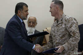 International Security Assistance Force (ISAF) commander General Joseph Dunford (R) and Afghan Defense Minister Bismillah Khan Mohammadi (L) shake hands during a ceremony handing over the Bagram prison to Afghan authorities, at the U.S. airbase in Ba