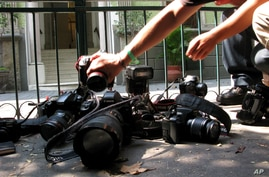 FILE - In this April 29, 2012, file photo, photojournalists place their cameras on the ground during a demonstration in Mexico City condemning the alleged murder of fellow journalist Regina Martinez, a correspondent for the Mexican investigative maga