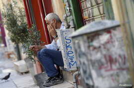 A vendor sits on the steps in front of his shop in central Athens, Greece, July 13, 2015.
