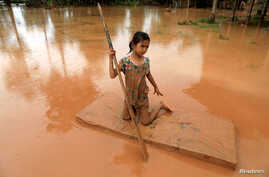 A girl uses a mattress as a raft during the flood after the Xe Pian Xe Namnoy hydropower dam collapsed in Attapeu province, Laos July 26, 2018.