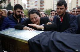 A relative cries over the coffin of Uygar Coskun, 32, killed in Saturday's bombing attacks, during his funeral, in Ankara, Turkey, Oct. 12, 2015.