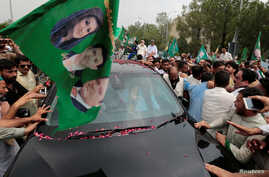 Supporters of former Pakistani Prime Minister Nawaz Sharif crowd around his car as his convoy leaves Islamabad, Pakistan, Aug. 9, 2017.