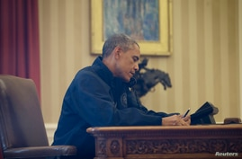 Through the window of the Oval Office, President Barack Obama is seen sitting at his desk at the White House in Washington, Oct. 12, 2014.