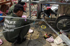 Thai police officers inspect the site of an explosion scene during an anti-government protest at Khao Saming district, Trat province, Feb. 23, 2014.