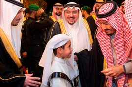 FILE - In this photo released by Saudi Press Agency, SPA, Saudi King Salman greets a boy during his visit to Qassim province in Qassim, Saudi Arabia, Nov. 7, 2018.