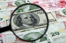 A U.S. 100 dollar banknote is seen through a magnifying lens on top of 10 and 20 lira banknotes in this illustration picture taken in Istanbul, Jan . 24, 2014.