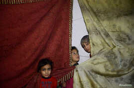Children stand near curtains in a shelter in the besieged town of Douma, Eastern Ghouta, in Damascus, Syria, March 11, 2018.