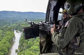 Venezuelan soldiers watch from the door of a helicopter as they patrol during a military operation to destroy clandestine drug laboratories, near the border with Colombia, in the state of Zulia, Dec. 6, 2014.
