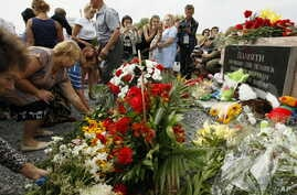 Local residents lay flowers to commemorate victims of the Malaysian Airlines plane, near the village of Hrabove, Donetsk region, eastern Ukraine, July 17, 2017.