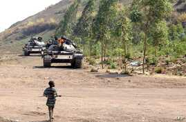 A young boy walks towards FARDC government forces tanks near the front line in Kanyaruchinya, 15km from Goma on July 24, 2013.
