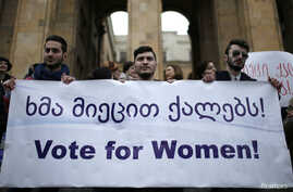 Men hold a banner during a protest demanding stronger women's political representation and engagement in parliament in front of the Parliament building on International Women's Day in Tbilisi, March 8, 2015. REUTERS/David Mdzinarishvili (GEORGIA - Ta...