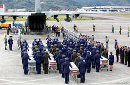 Military personnel unload a coffin with the remains of Brazilian victims who died in a plane crash in the Colombian jungle with Brazilian soccer team Chapecoense. The bodies will be flown home to Brazil, Dec. 2, 2016.