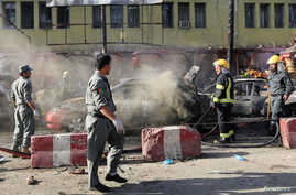 Afghan policemen inspect the site of a blast in Jalalabad city, Afghanistan, July 1, 2018.