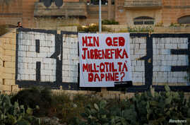 "A protest banner reading ""Who is benefitting from Daphne's murder?"", referring to the assassination of anti-corruption journalist Daphne Caruana Galizia in October 2017, hangs over a tunnel entrance in St Julian's, Malta April 23, 2018."