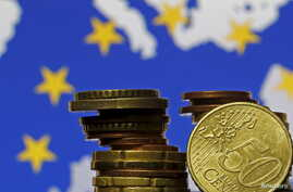 Euro coins are seen in front of displayed flag and map of European Union in this picture illustration taken in Zenica, Bosnia and Herzegovina, May 28 2015.