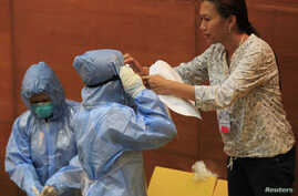 "A Philippine health worker assists a colleague with protective suits and equipment during the ""One Nation, One Direction for EBOLA Prevention"" training at the Research Institute for Tropical Medicine hospital in Alabang, Muntinlupa, south of Manila,"