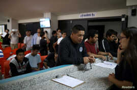 FILE - People deported from the U.S. wait to make a phone call to the U.S. at an immigration facility in San Salvador, El Salvador, July 3, 2018.