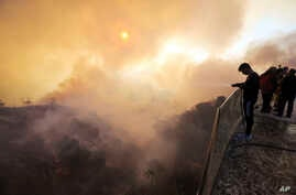Aaron Kaboud sprays water off the deck of his family's home that was spared by a wildfire that hit the Bel Air district of Los Angeles, Dec. 6, 2017.