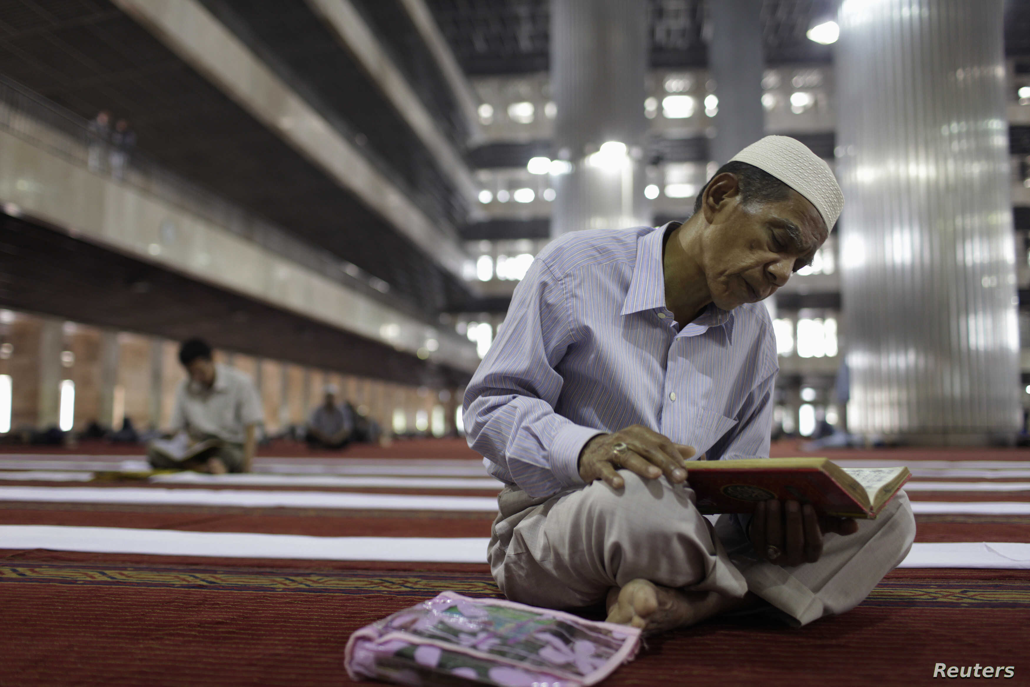 FILE - A man reads the Koran at Istiqlal mosque in Jakarta, July 24, 2012.