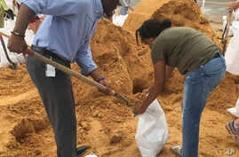Tallahassee Mayor and Democratic gubernatorial candidate, Andrew Gillum, left, helps Eboni Sipling fill up sandbags in Tallahassee, Florida, Oct. 8, 2018.