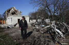A man walks past a residential building and car damaged by recent shelling in Donetsk, eastern Ukraine, Nov. 6, 2014.